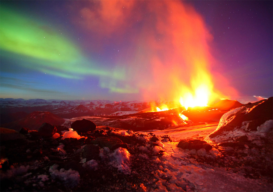 erupting volcano with northern light, iceland