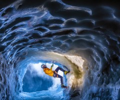 climbing in a glacial ice cave in the alps