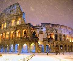 snowfall over colosseum in rome, italy