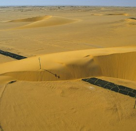 road interrupted by a sand dune