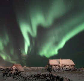aurora borealis over cabins in iceland