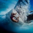 girl swimming underneath wave