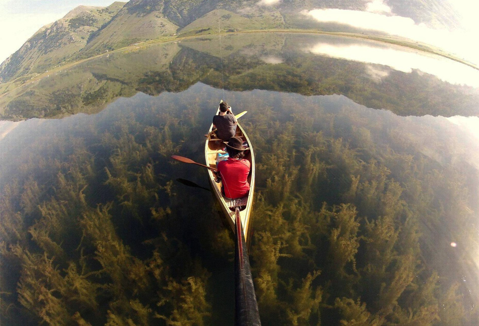 canoeing in a crystal clear lake, italy