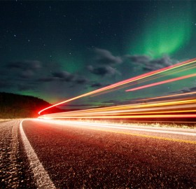 northern lights over roads of alaska