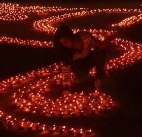 girl lights earthen lamps, india