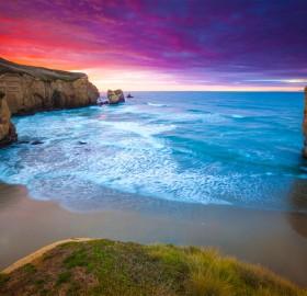 colourful sunrise over tunnel beach, new zealand