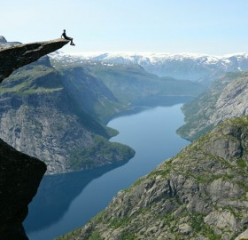 sitting on the edge of trolltunga, norway