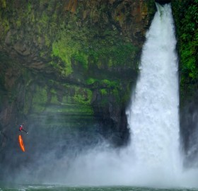 man jumps from a cliff next to a waterfall, veracruz, mexico